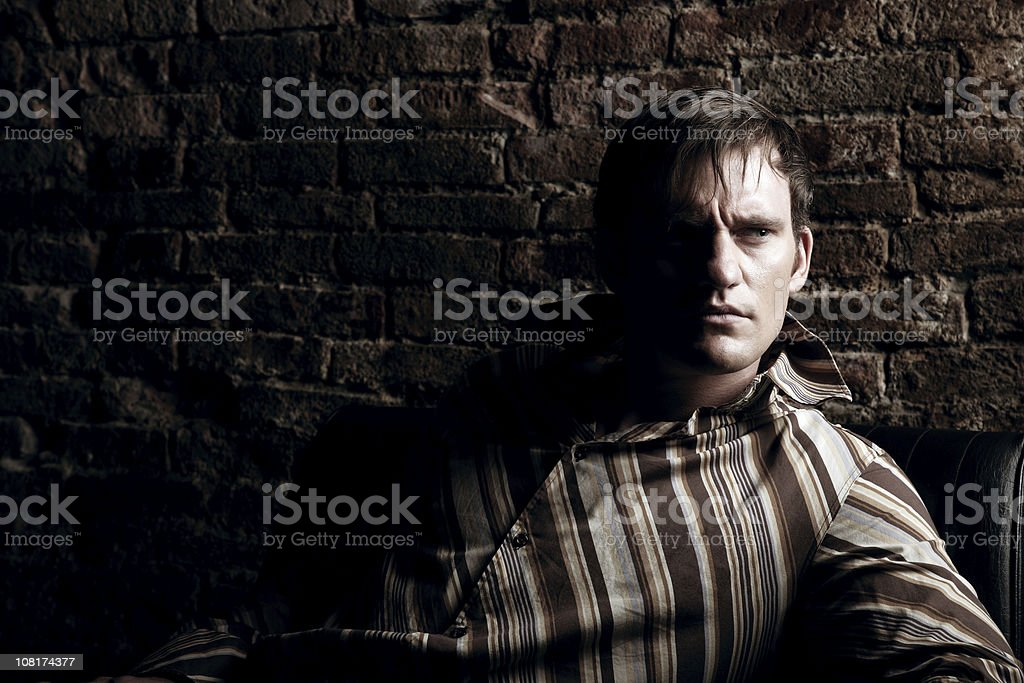 Young Man Sitting Against Brick Wall, Low Key royalty-free stock photo