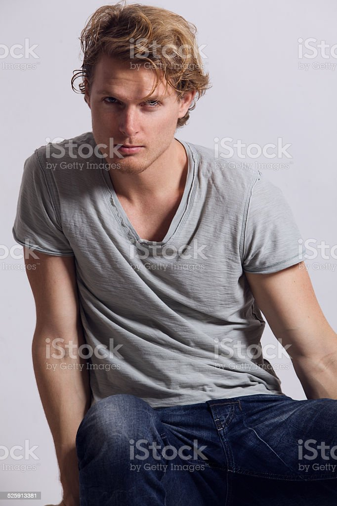 Young man sitting and looking at camera stock photo
