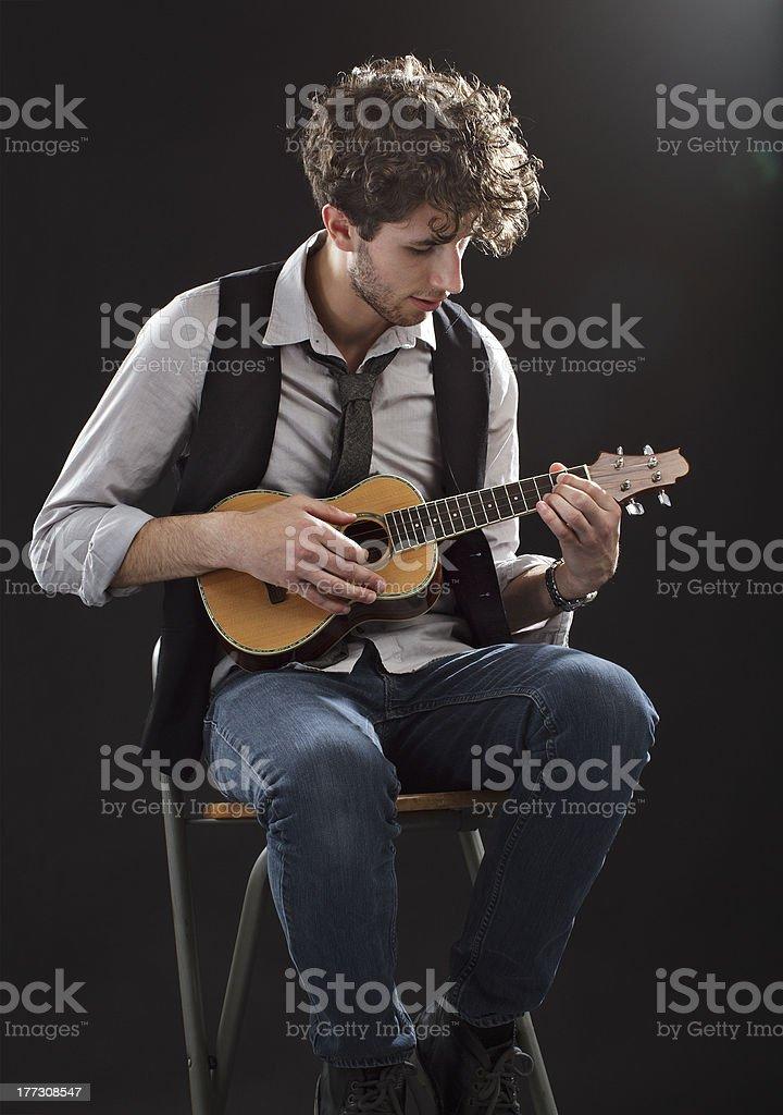 Young man sitting and playing a ukulele stock photo