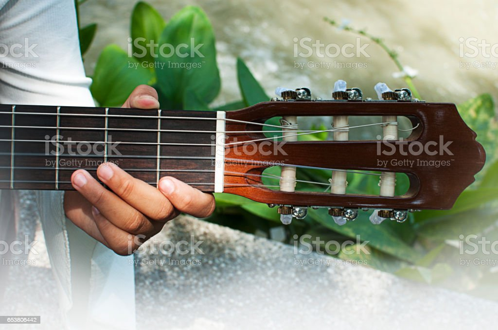 Young man sitting and playing guitar in the park stock photo