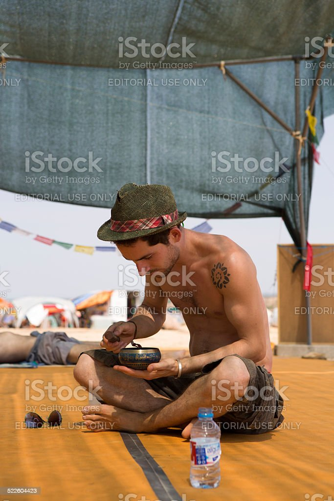 Young man sitting and practicing the Tibetan bowl singing stock photo