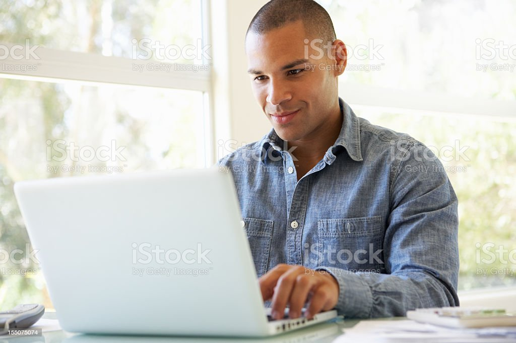 Young man sitting at a table using a laptop stock photo