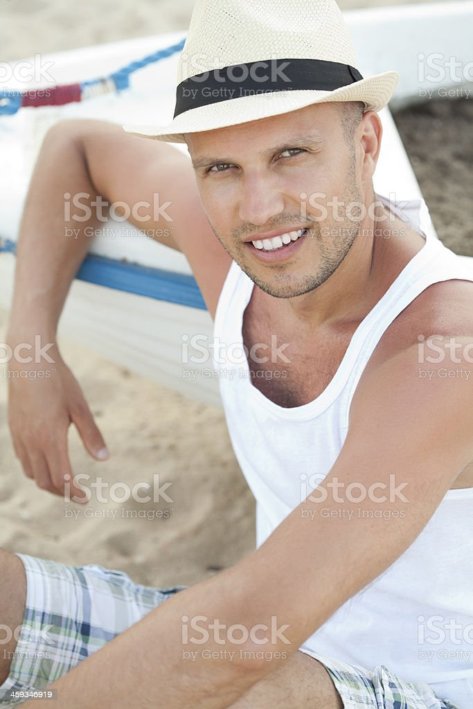 young man sitting at beach stock photo