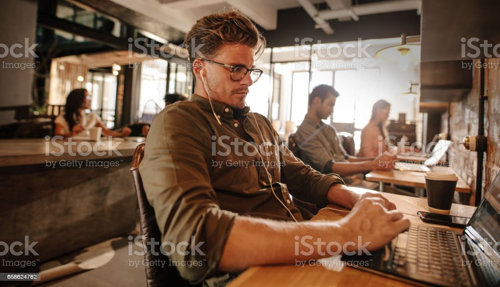 Young man sitting at cafe and using laptop stock photo