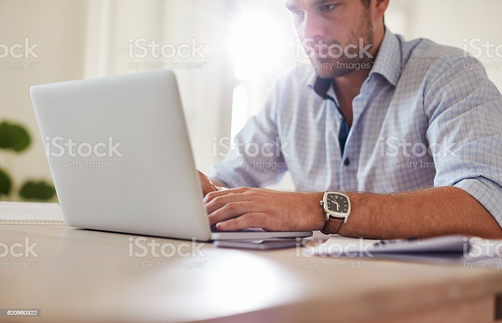 Young man sitting at table and using laptop stock photo