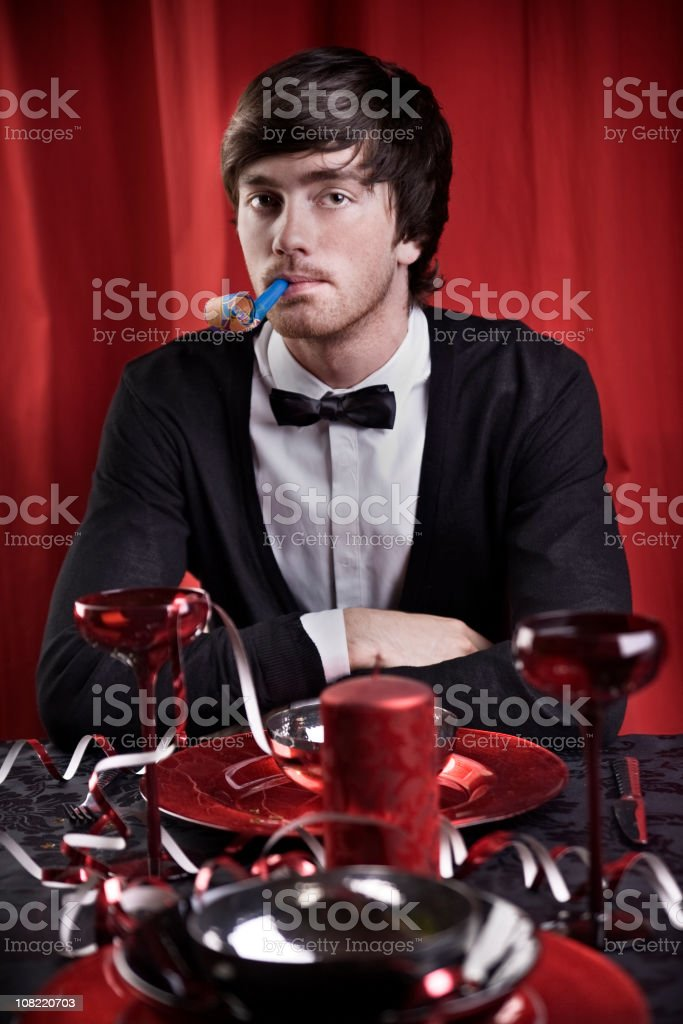 Young Man Sitting at Table Blowing Party Horn Blower royalty-free stock photo