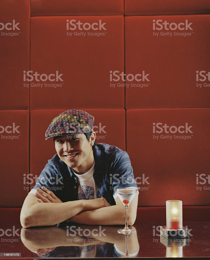 Young man sitting at table in nightclub, smiling, portrait royalty-free stock photo