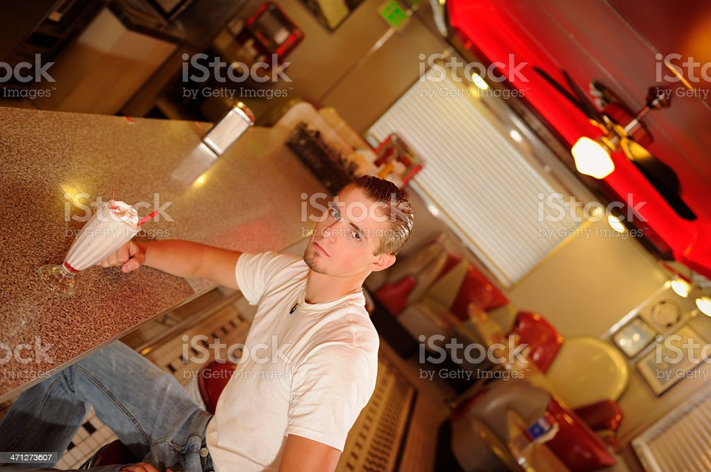 Young Man Sitting At The Counter In Retro Diner stock photo