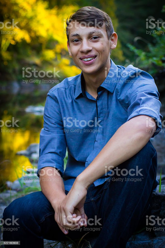 Young Man Sitting By The River stock photo