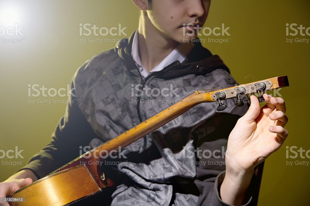 Young man sitting guitar tuning stock photo