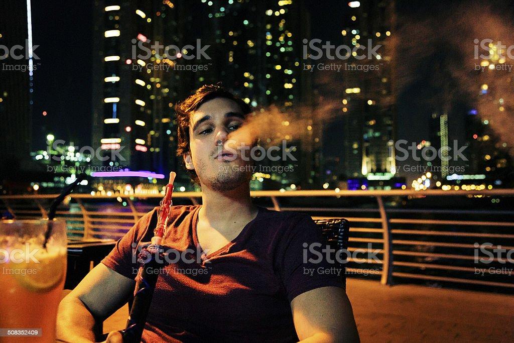 young man sitting in cafe, smoking shisha stock photo