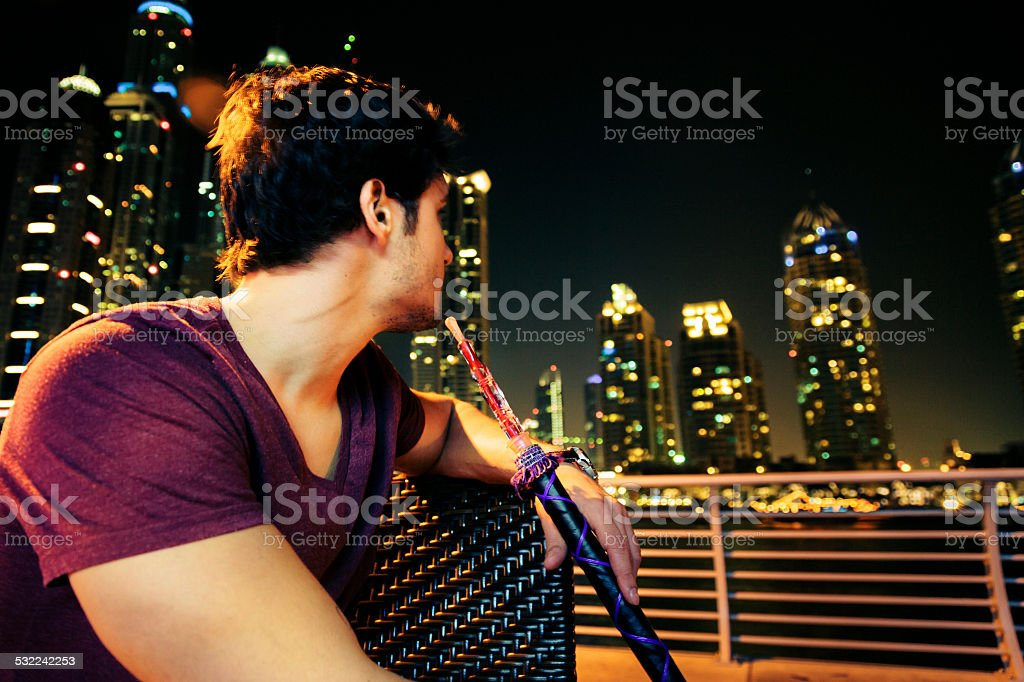 young man sitting in cafe, smoking shisha stock photo
