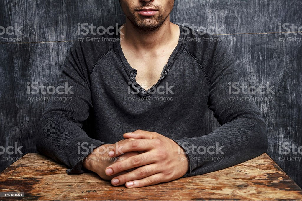 Young man sitting in front of blackboard royalty-free stock photo