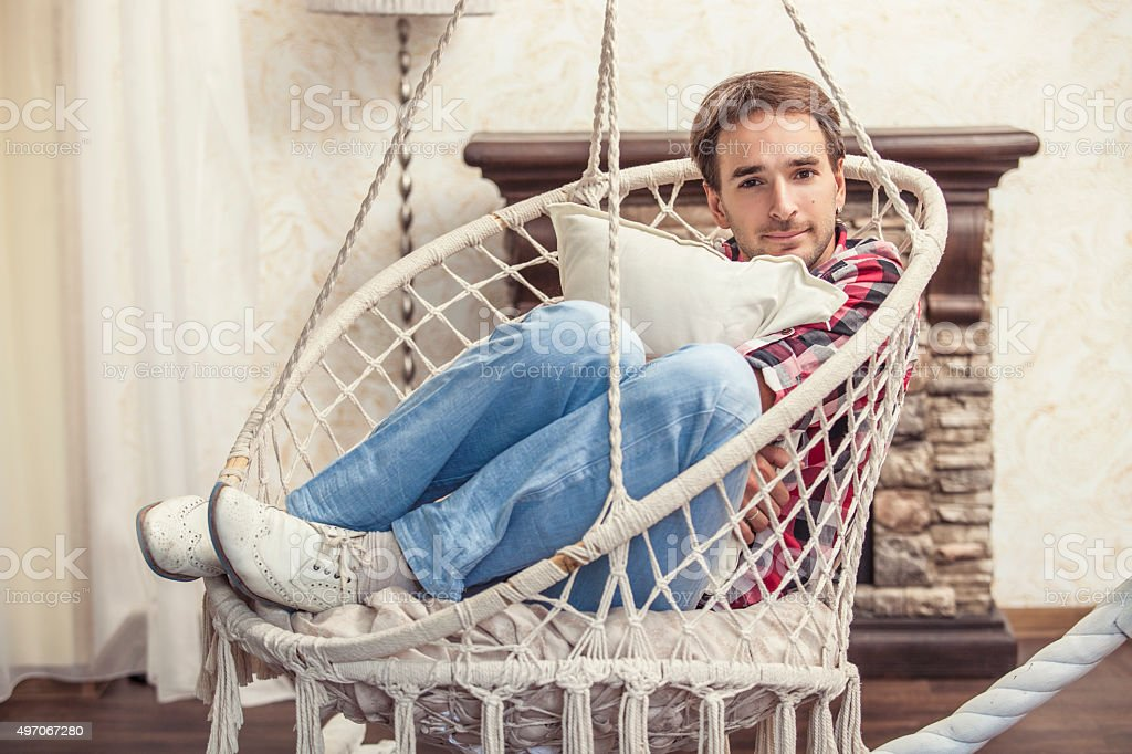 Young man sitting in the hanging chair resting at home stock photo