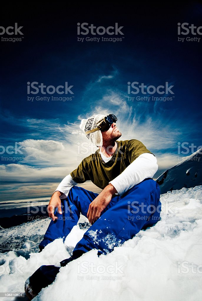 Young man sitting in the snow royalty-free stock photo