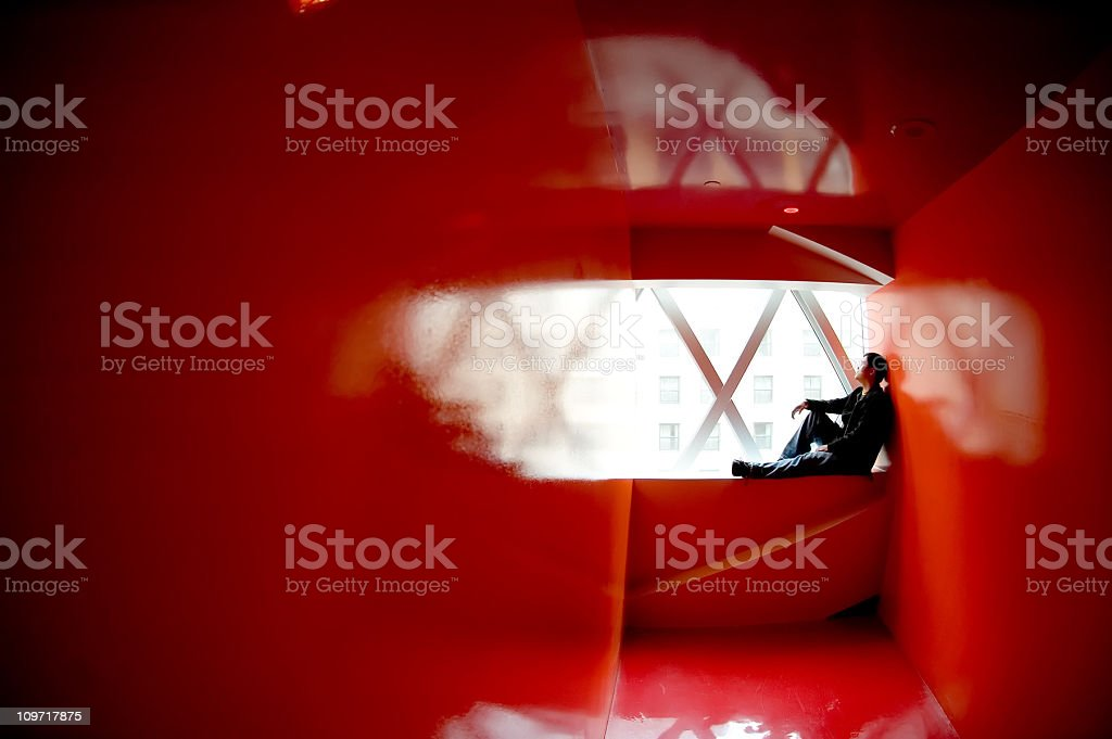 Young Man Sitting in Windowsill of Red Room royalty-free stock photo