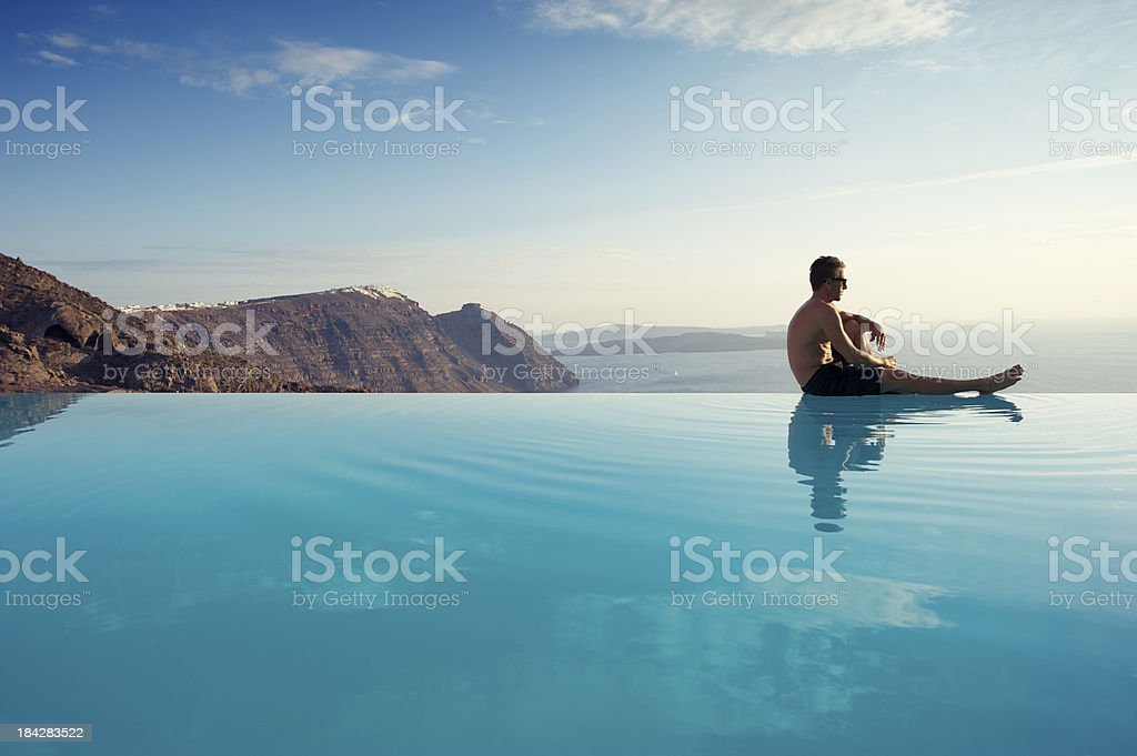 Young Man Sitting Infinity Pool Edge Caldera View Santorini Greece stock photo