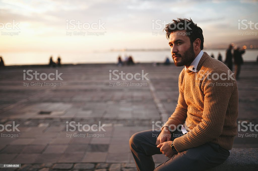 Young man sitting looking away stock photo