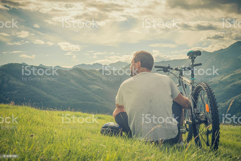 Young man sitting near bike looking at panorama on mountain stock photo