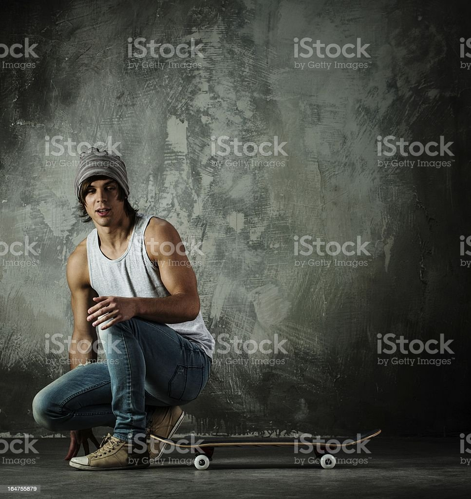 Young man sitting near skateboard royalty-free stock photo