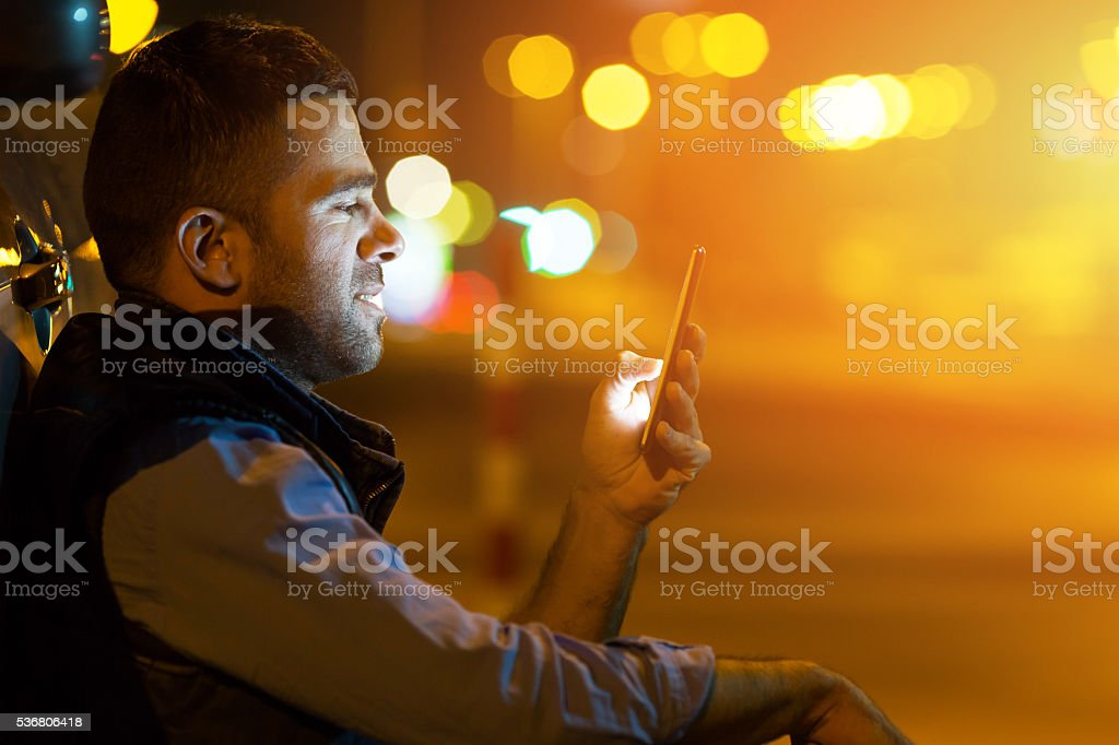 Young man sitting next to his cat at night stock photo