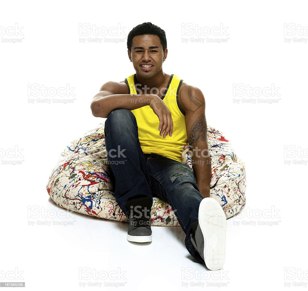 Young man sitting on a bean bag royalty-free stock photo