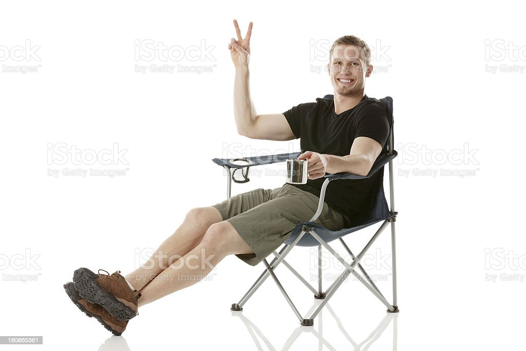 Young man sitting on a chair gesturing victory sign royalty-free stock photo