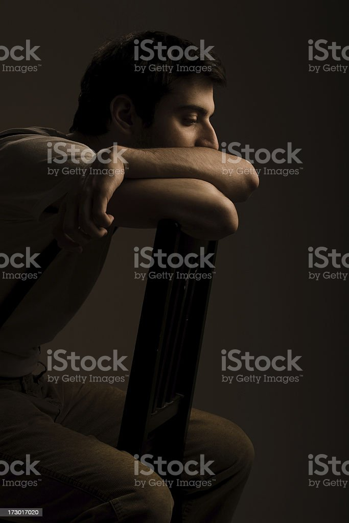 Young man sitting on a chair stock photo