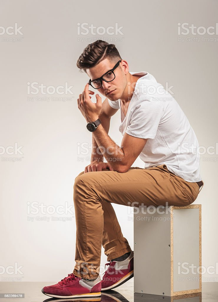 young man sitting on a chair thinking stock photo