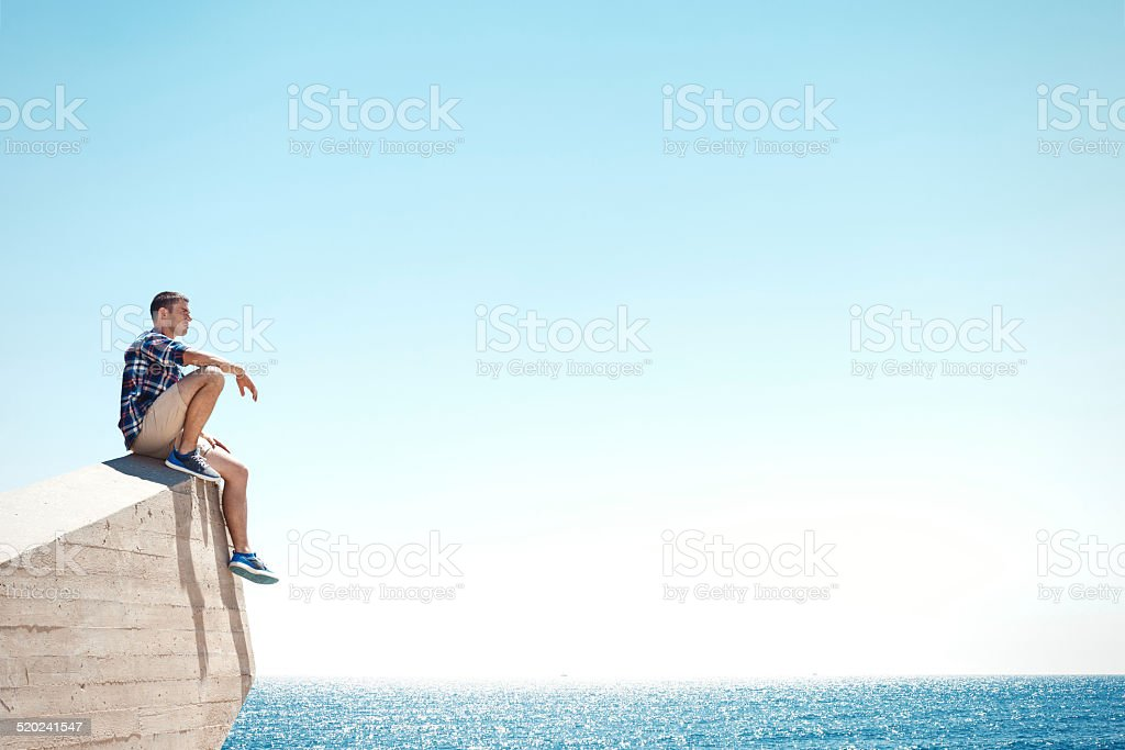 Young man sitting on a cliff stock photo