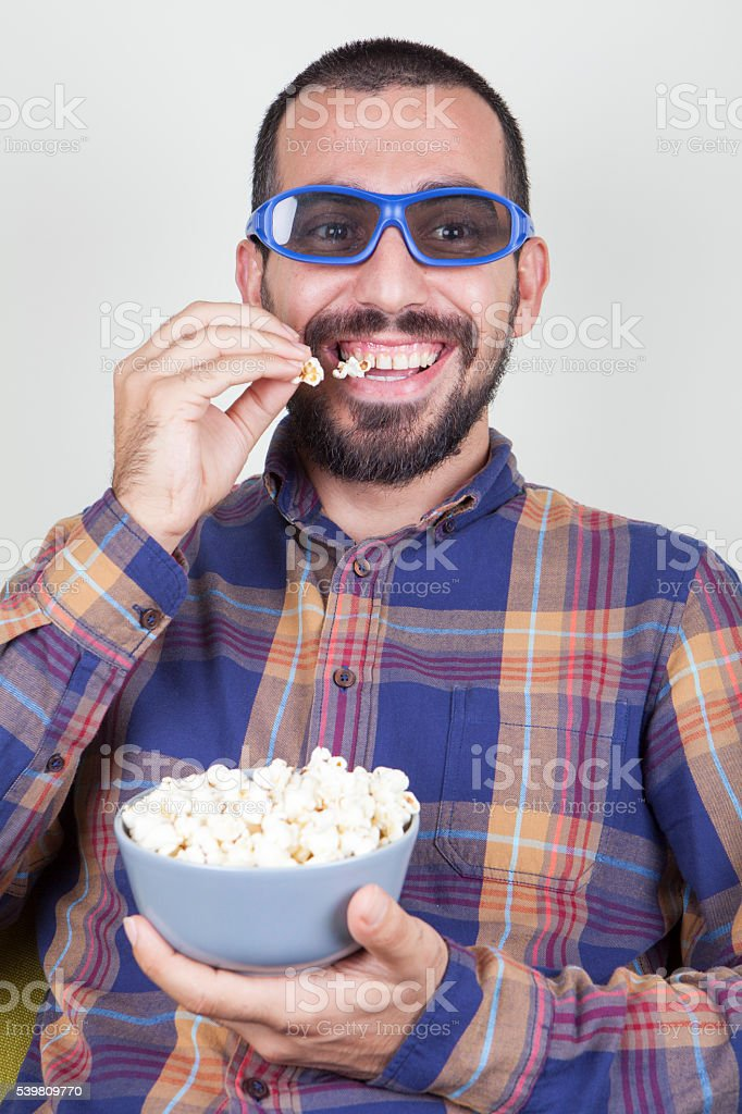 Young man sitting on a couch while watching TV stock photo