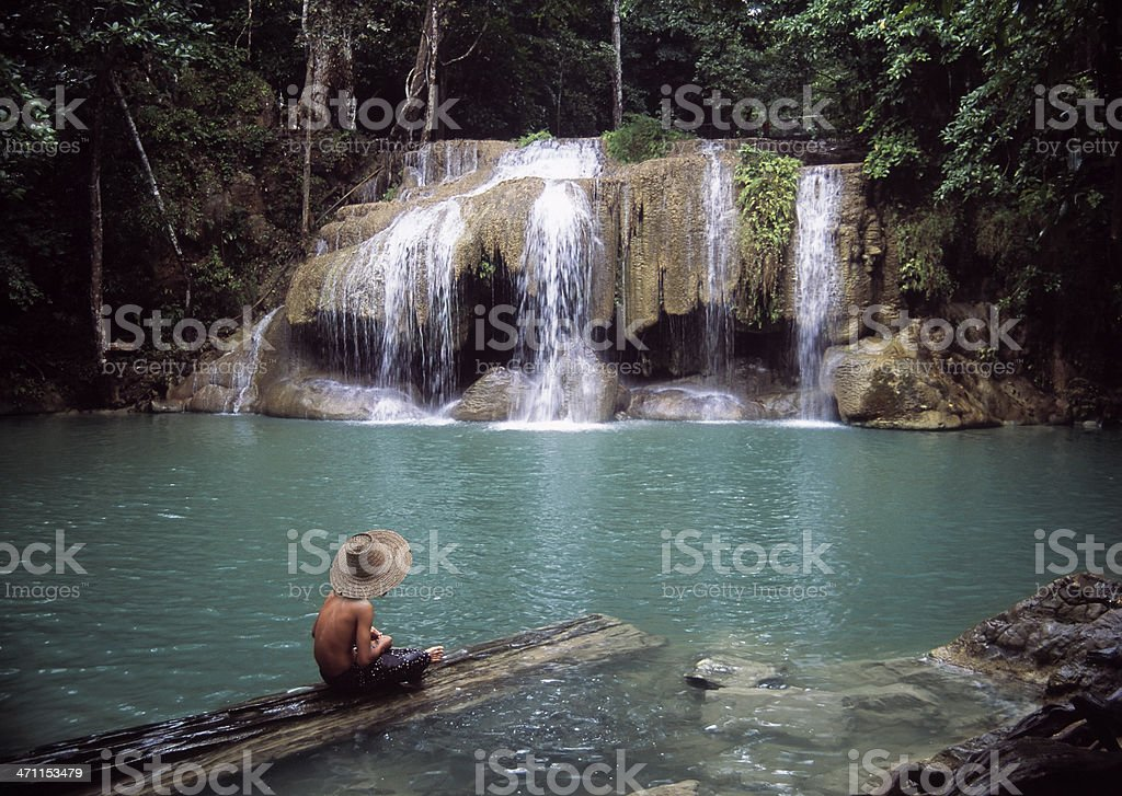 Young Man Sitting on a log beside waterfall stock photo