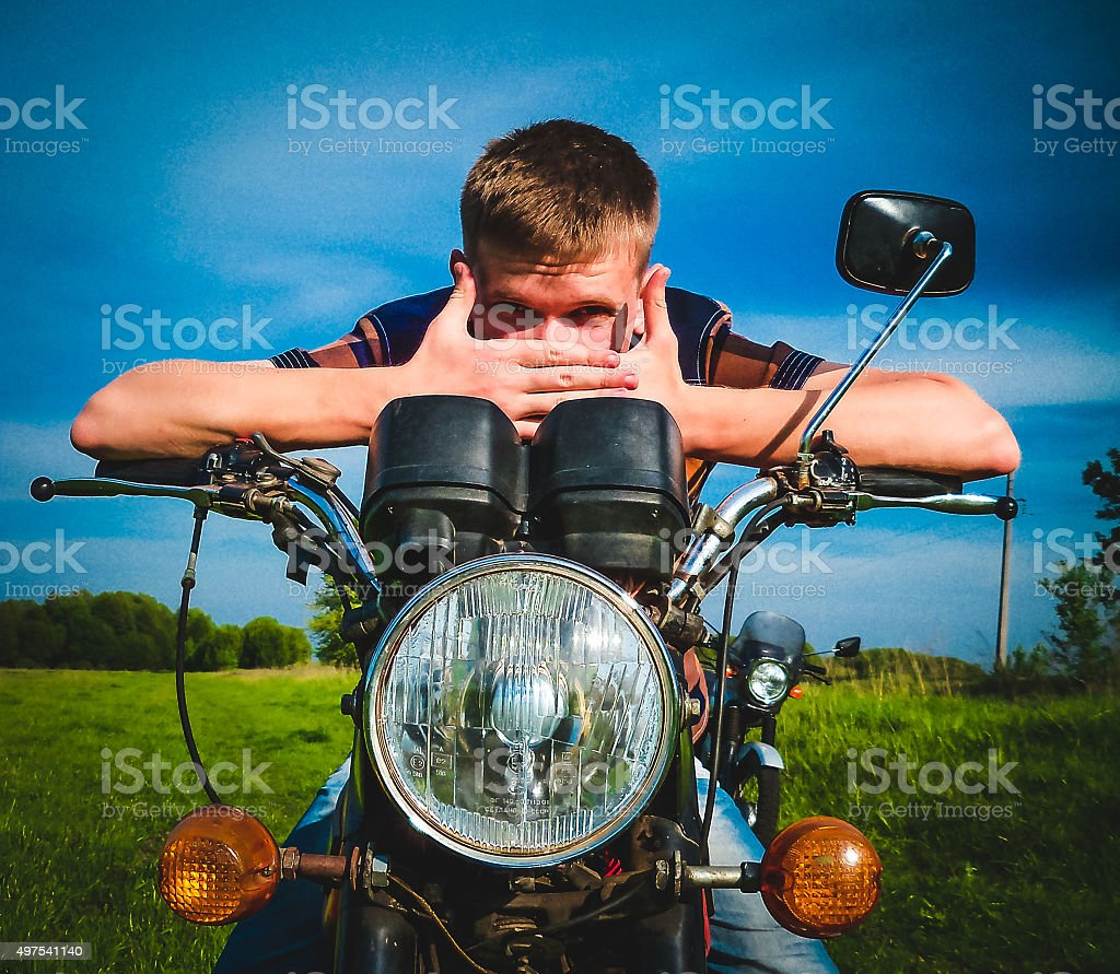young man sitting on a motorcycle stock photo