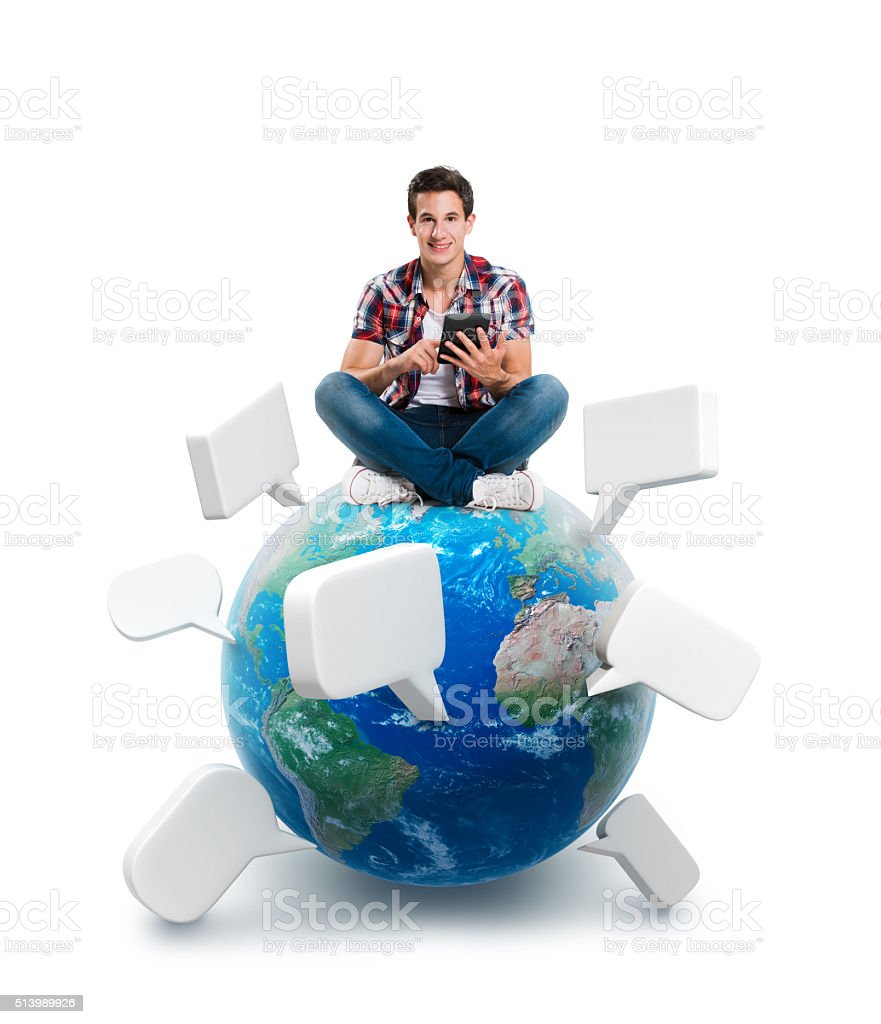 Young man sitting on a planet with a tablet stock photo