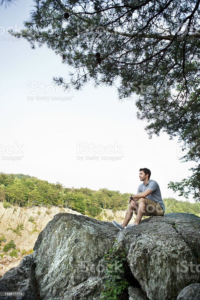 Young Man Sitting on a Rock royalty-free stock photo