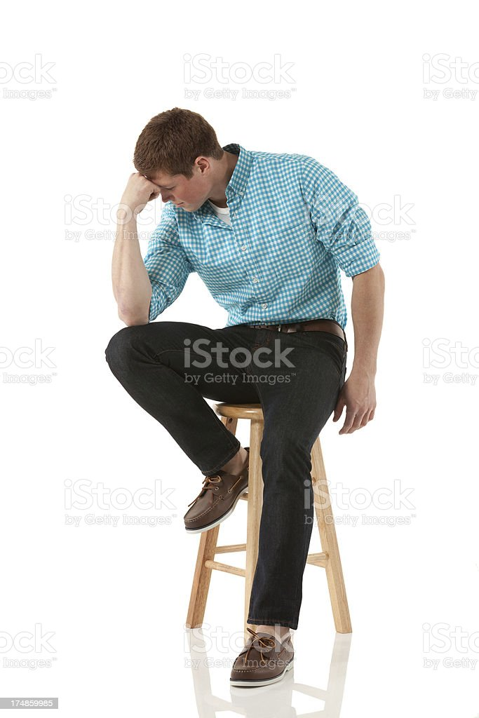 Young man sitting on a stool and thinking royalty-free stock photo