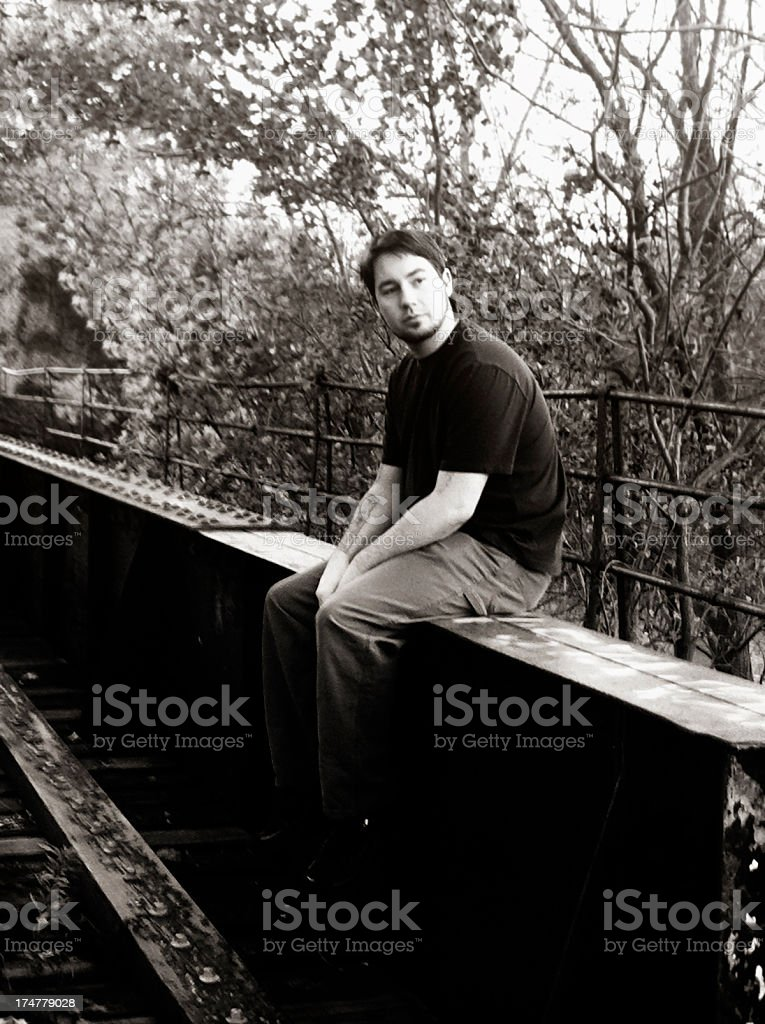 Young Man Sitting On An Old Train Bridge stock photo