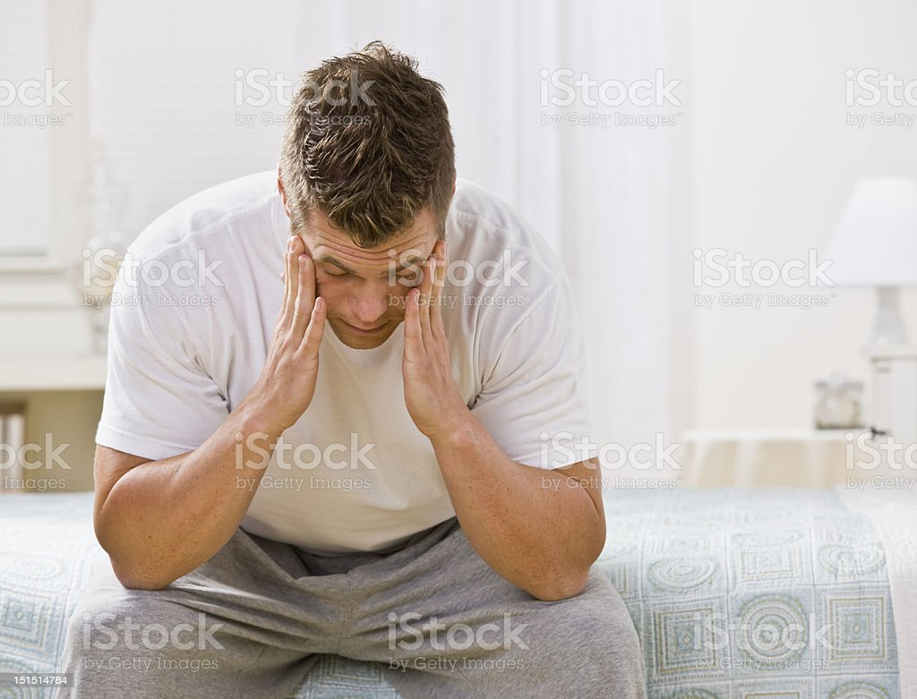 Young Man Sitting on Bed stock photo