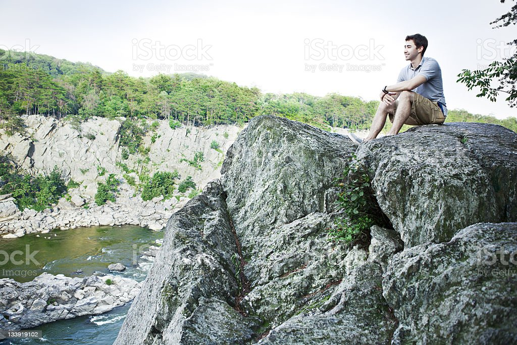 Young Man Sitting on Cliff stock photo