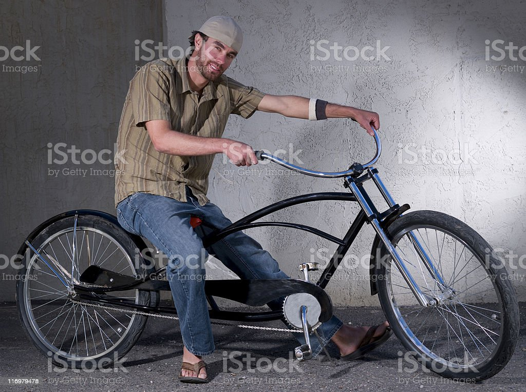 Young man sitting on cruiser bicycle royalty-free stock photo