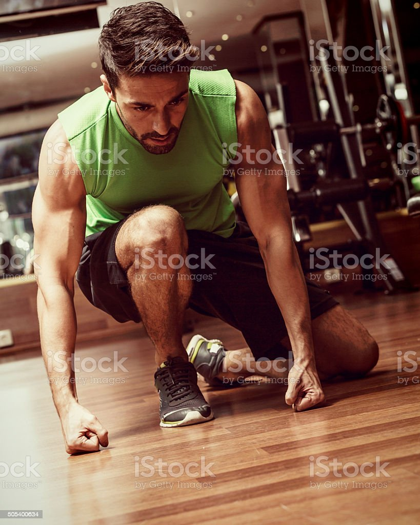 Young Man Sitting on Floor in Gym stock photo