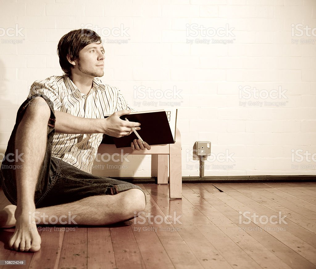 Young Man Sitting on Floor Reading Book stock photo