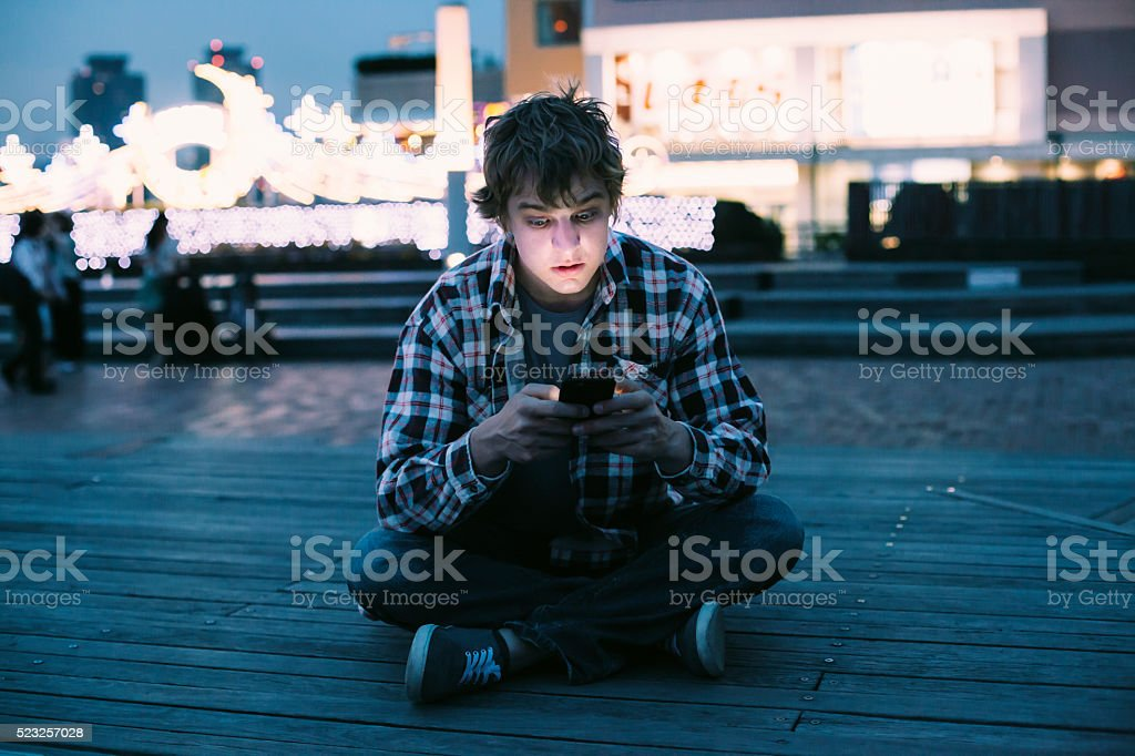 Young man sitting on ground and typing on phone stock photo