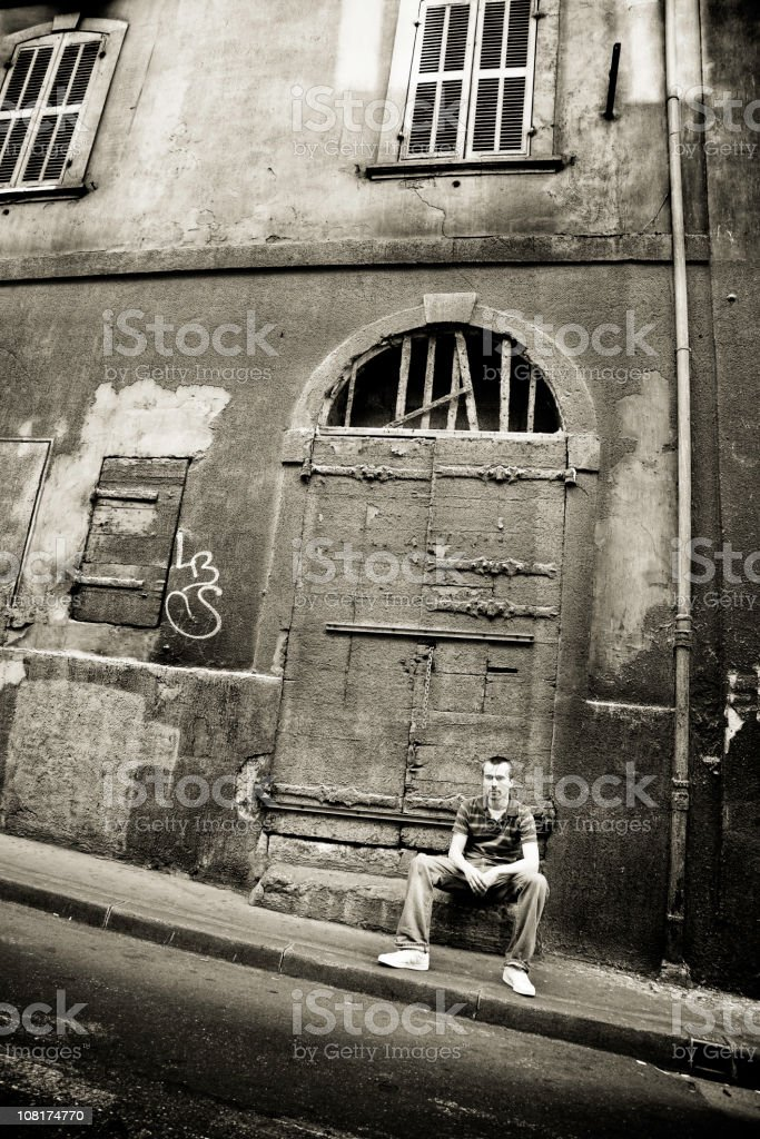 Young Man Sitting on Grunge Street, Black and White royalty-free stock photo