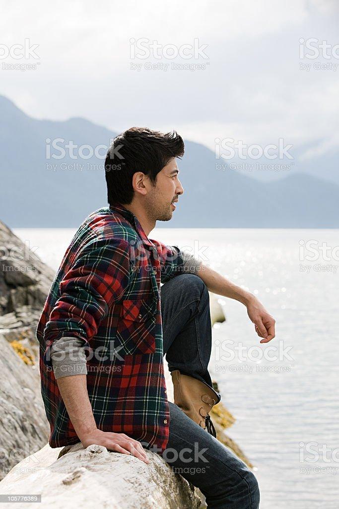 Young man sitting on log near lake royalty-free stock photo