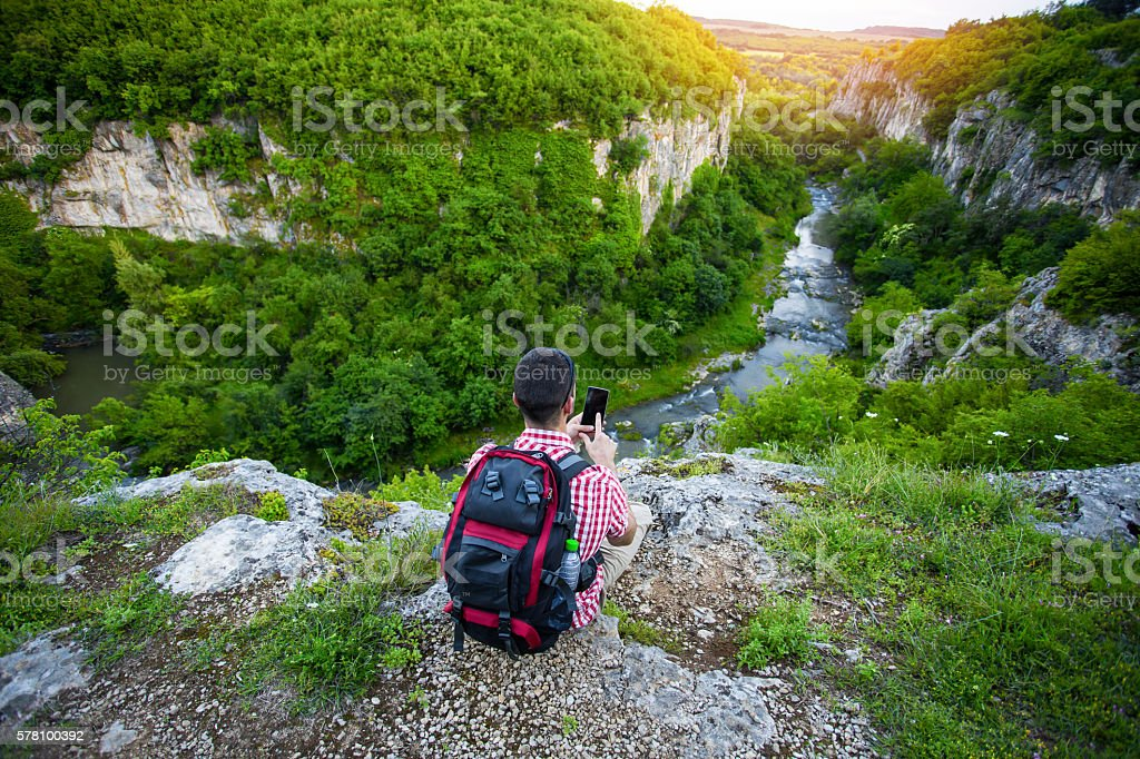 Young man sitting on mountain peak and typing on phone stock photo