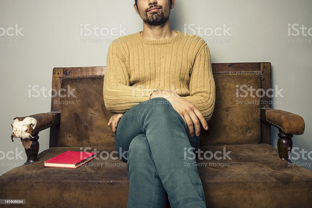 Young man sitting on old sofa with book royalty-free stock photo