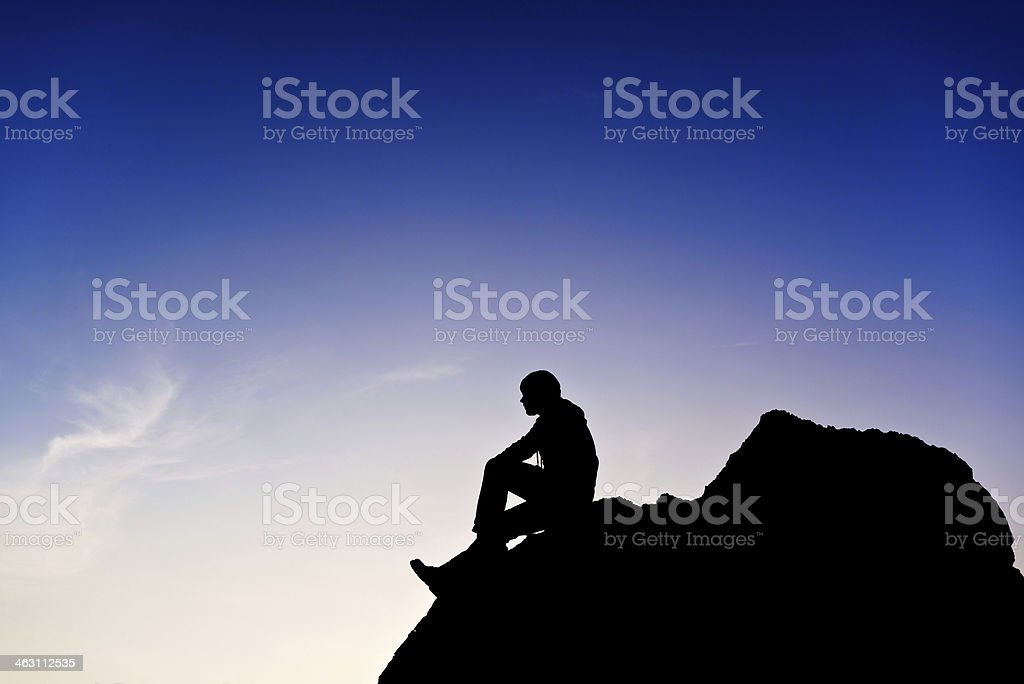 Young man sitting on rocky royalty-free stock photo