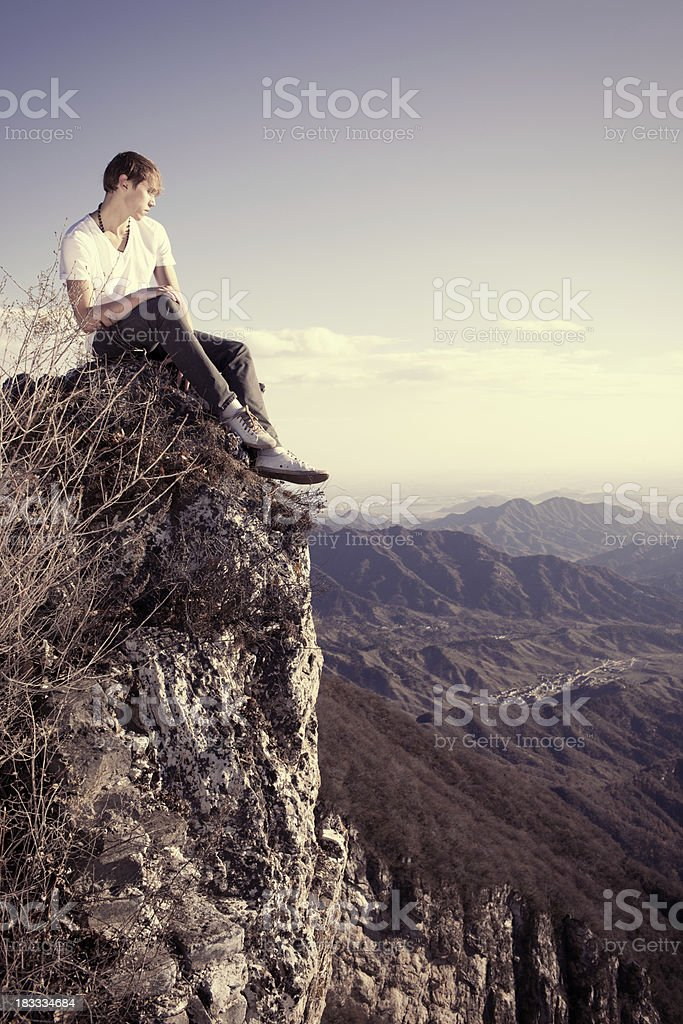 Young man sitting on the cliff royalty-free stock photo