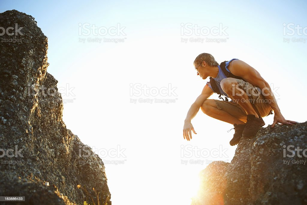 Young man sitting on the edge of a rock stock photo